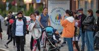 Люди стоят на автобусной остановке на фоне лайтбокса с логотипом национальной переписи населения