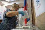 Избирательница опускает бюллетень в урну для голосования на выборах в Госдуму России