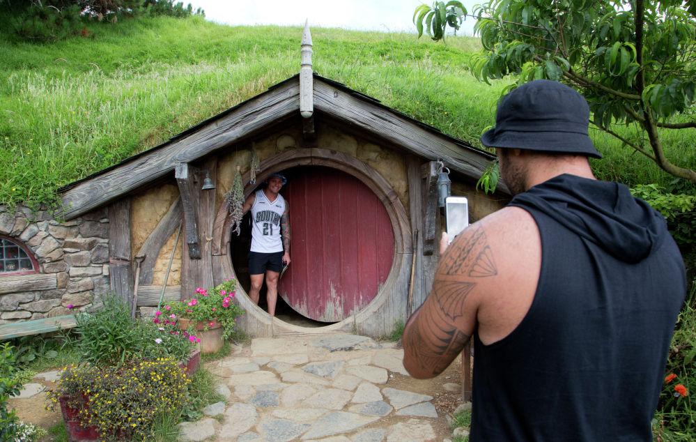 Турист фотографируется возле домика хоббита в Новой Зеландии