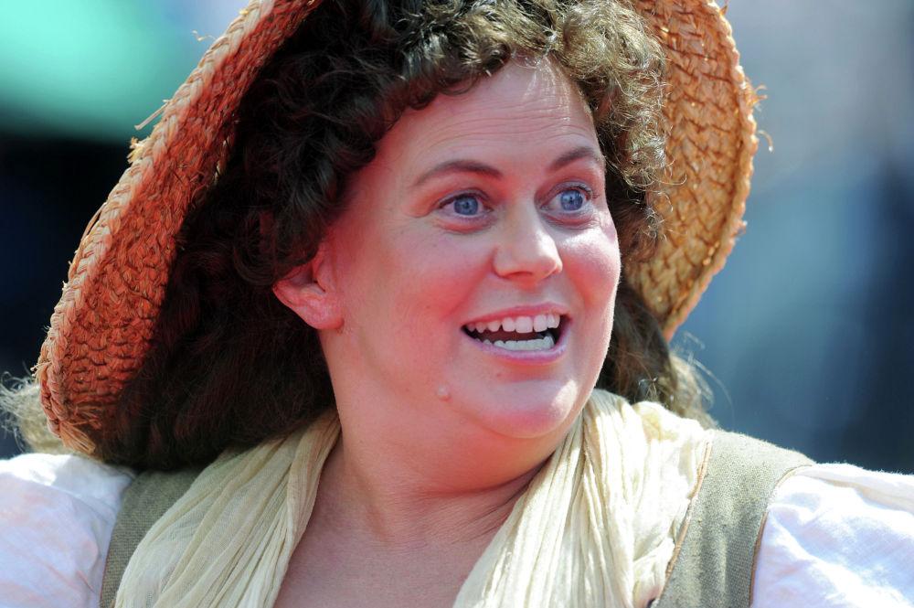 Актриса в костюме жительницы Хоббитона приветстсвует зрителей премьеры фильма Хоббит: неожиданное путешествие