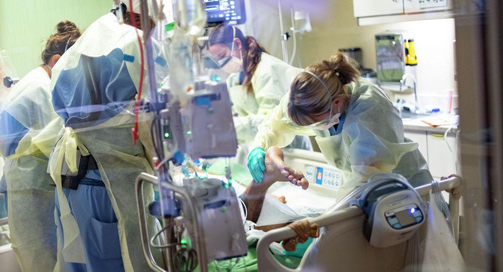 Медики в защитных костюмах ухаживают за пациентом в отделении интенсивной терапии в больнице с коронавирусом