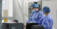 Медики в защитных костюмах работают в отделении реанимации в больнице с коронавирусом