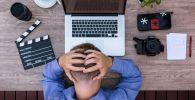 Человек хватается за голову, сидя за компьютером