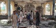 Люди в разрушенной взрывом мечети в провинции Кундуз