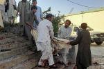 Люди выносят из мечети тела жертв и пострадавших от взрыва