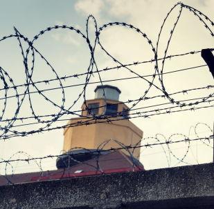 Тюремная башня за забором с колючей проволокой