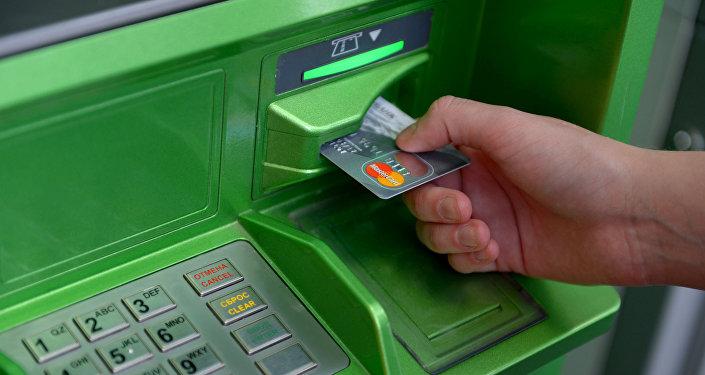 Архивное фото человека у банкомата с платежной картой