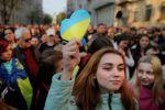 Девушка держит бумажное сердце в цветах украинского флага
