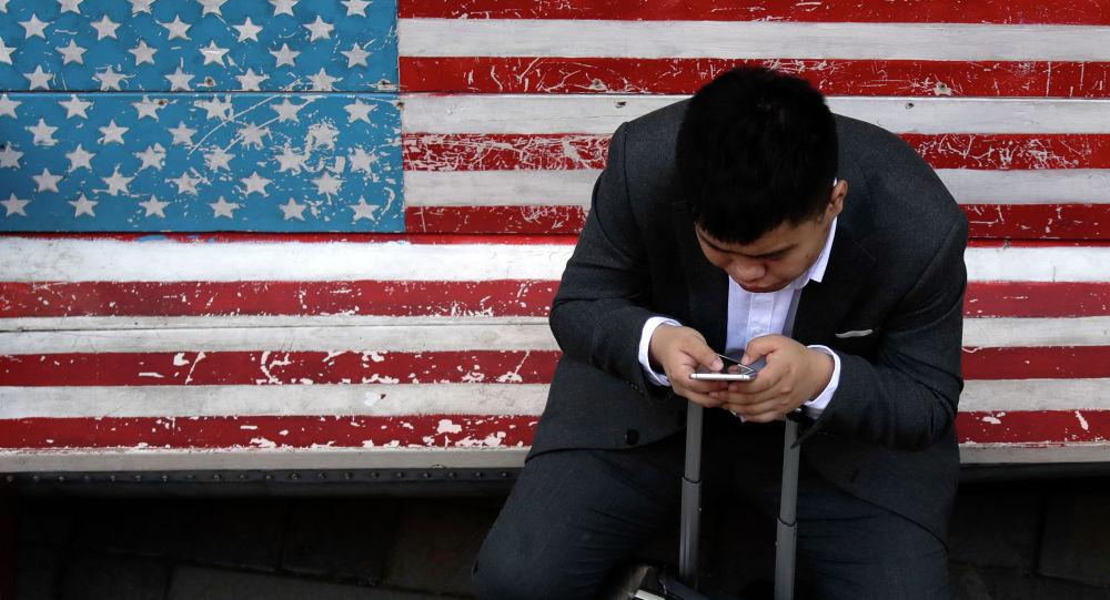Мужчина сидит на скамейке, раскрашенной в цветах американского флага