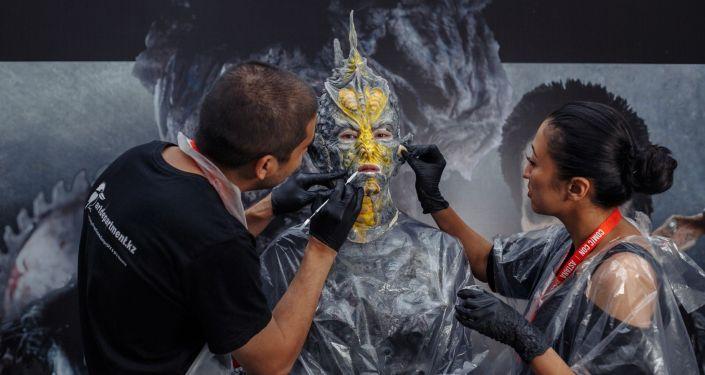 Художники накладывают грим на участника косплея