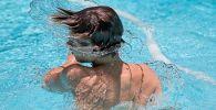 Мальчик купается в бассейне