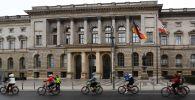 Велосипедисты едут мимо здания Палаты депутатов Берлина.