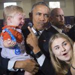 Президент США Барак Обама в окружении сторонников, делающих с ним селфи.