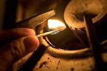 Архивное фото газовой конфорки и заженной спички в руке