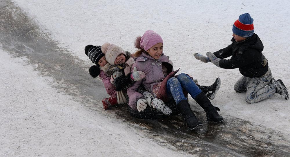 Дети катаются на ледяной горке