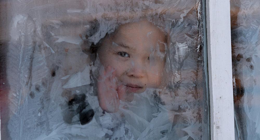Девочка смотрит в заиндевелое окно, архивное фото