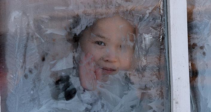 Девочка смотрит в заиндевелое окно