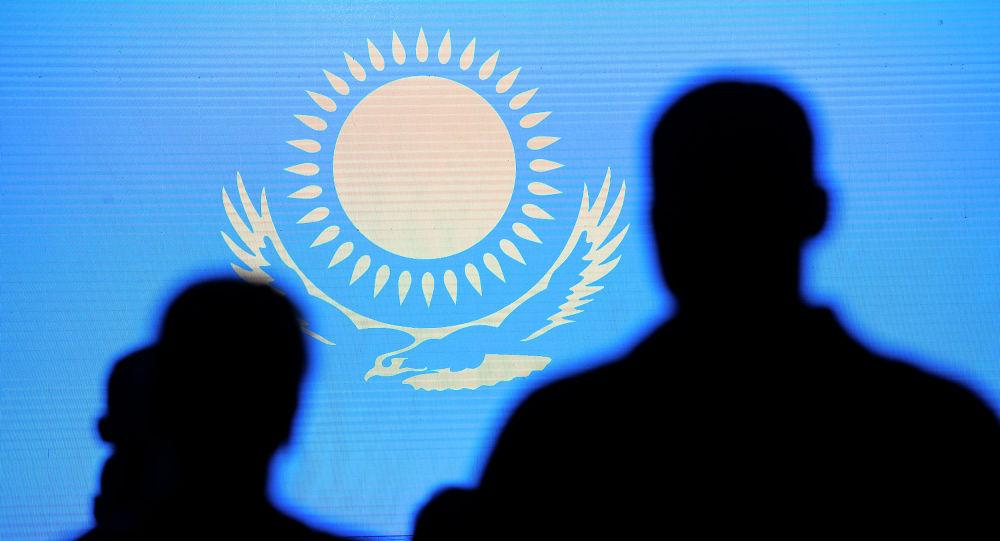 Силуэты людей на фоне флага Казахстана