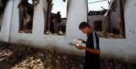 Мальчик у стены разрушенного дома, архивное фото