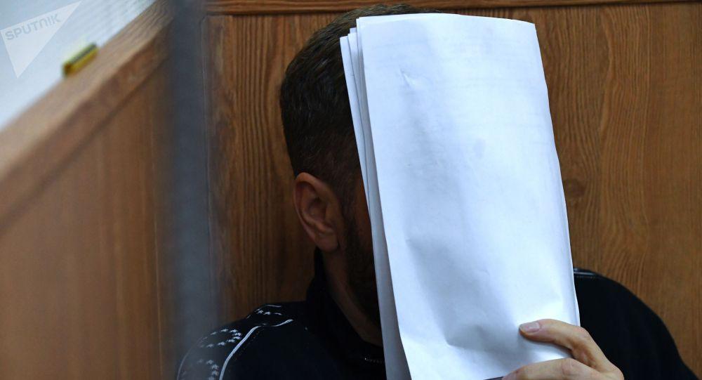 Обвиняемый, закрывший лицо листом бумаги. Архивное фото