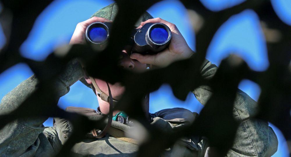 Российский военный смотрит в бинокль
