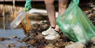 Девушка собирает мусор в пакет, иллюстративное фото