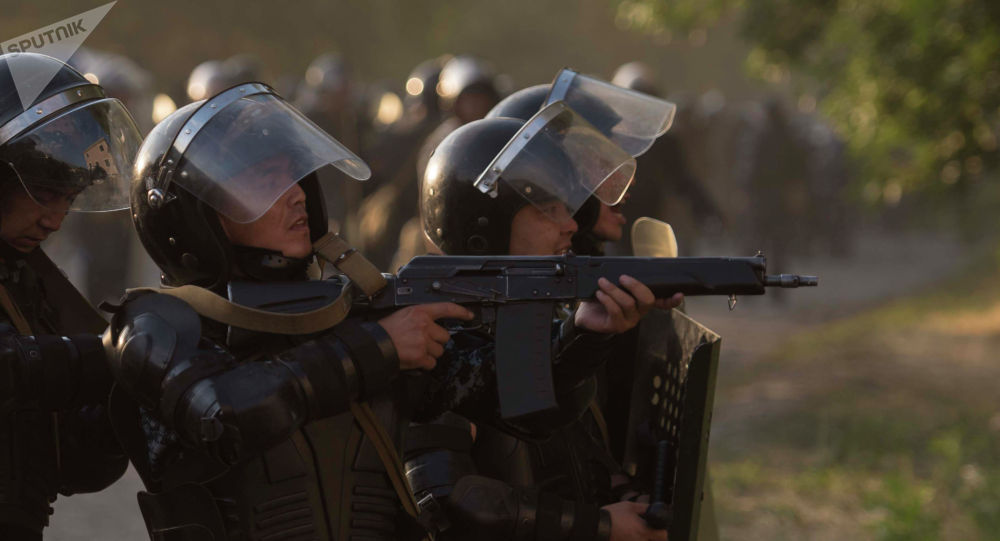 Полицейский нацеливает автоматическую винтовку, архивное фото