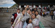 Одетые в традиционные корейские платья посетители фотографируются перед павильоном во дворце Кёнбоккун в Сеуле, архивное фото