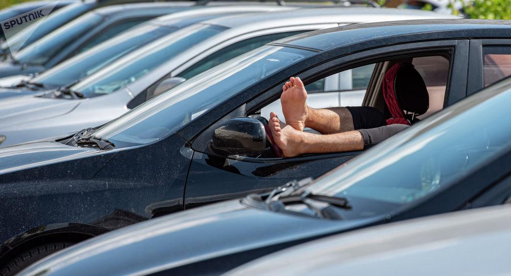 Мужские ноги в окне машины в жару