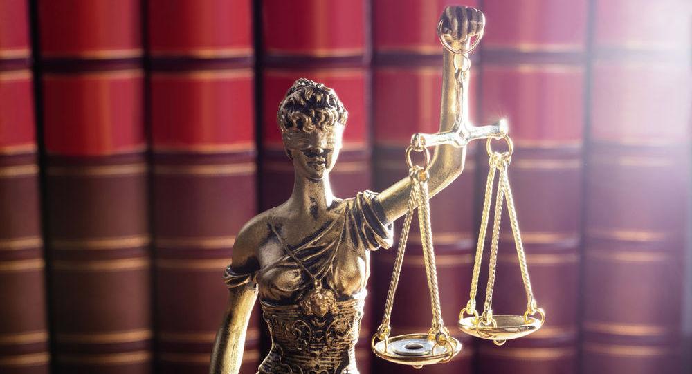 Золотая статуя богини правосудия Фемиды на фоне книг