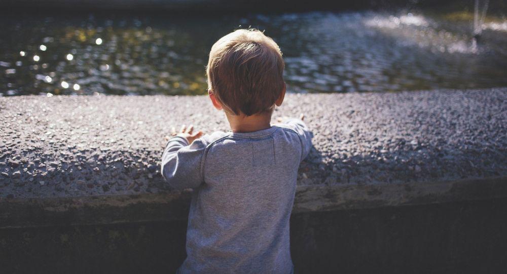 Мальчик у водоема, иллюстративное фото