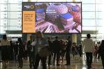 Люди проходят перед рекламным щитом Dubai Expo 2020