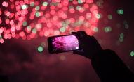 Девушка снимает на смартфон фейерверк