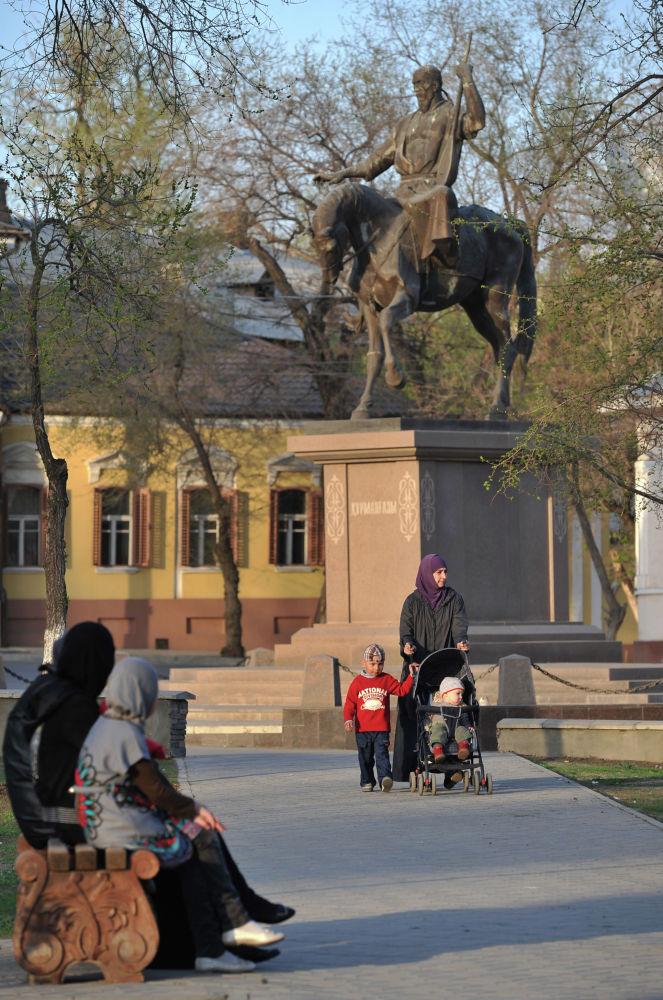 Женщины с детьми у памятника казахскому народному музыканту Курмангазы Сагырбаеву в Астрахани