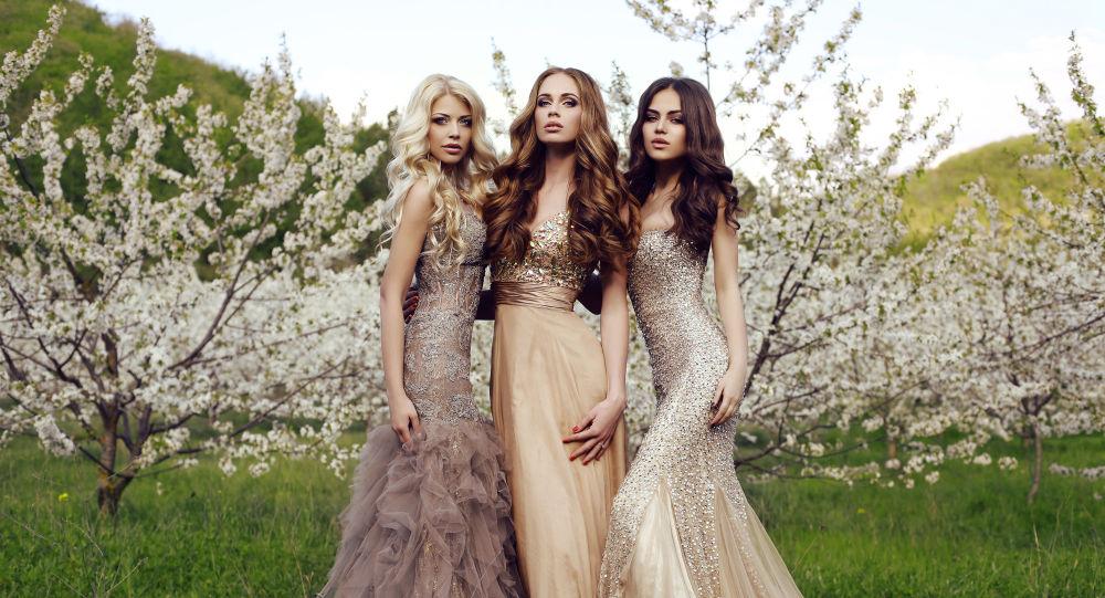 Три красивые девушки с длинными волосами и макияжем, одетые в вечерние платья, позируют в весеннем саду