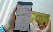 Карточка Kaspi bank и смартфон, иллюстративное фото