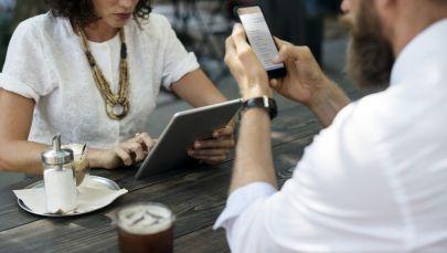 Девушка и парнеь за столиком в кафе смотрят в гаджеты, иллюстративное фото