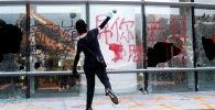 Протестующий бросает камень в здание политехнического университета в Гонконге, Китай
