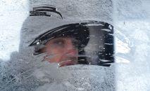 Мужчина смотрит в замерзшее окно, архивное фото