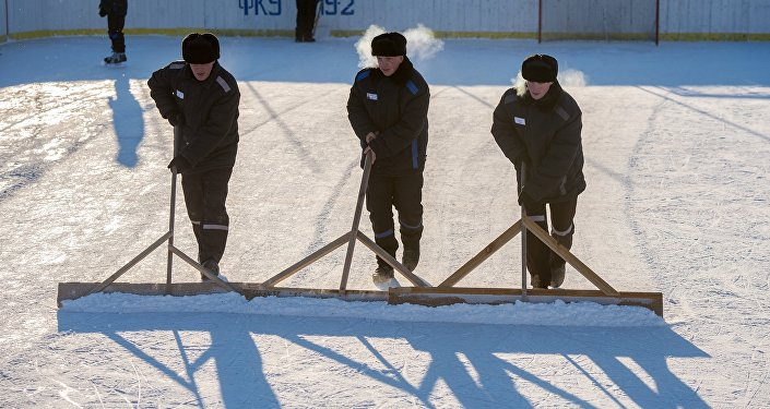 Заключенные расчищают игровое поле перед хоккейным матчем в лечебно-исправительном учреждении