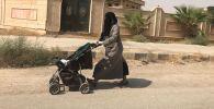 Женщина с детской коляской на улице в Сирии, архивное фото