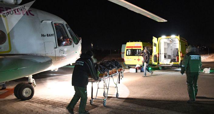 Сотрудники службы медицинских катастроф транспортируют пострадавшего в реанимобиль