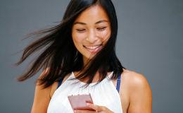 Симпатичная девушка с развевающимися волосами стоит со смартфоном в руках на голубом фоне и улыбается