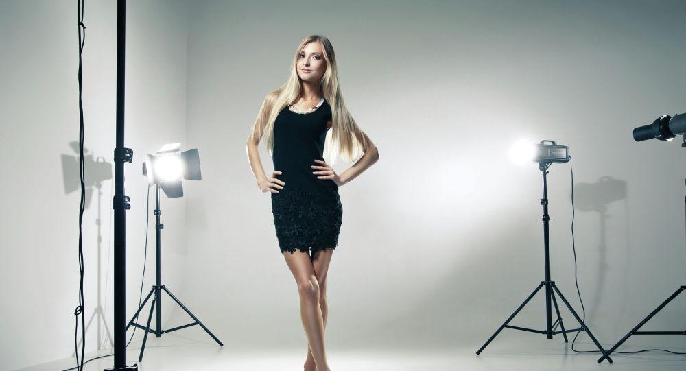 Красивая девушка блондинка с длинными волосами в черном платье позирует в фотостудии