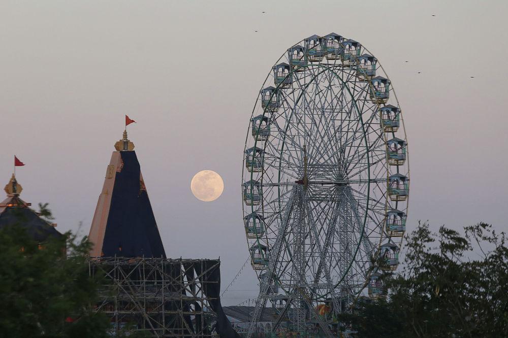Полнолуние встает за колесом обозрения в парке развлечений в Бхопале