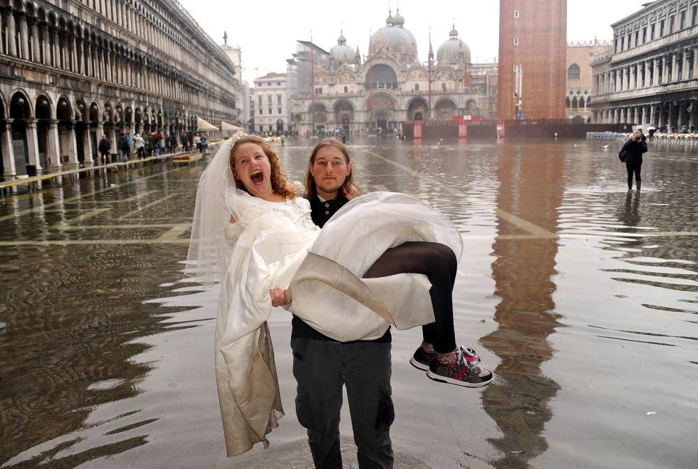 Венецияны су басты. Қалыңдығын қолына көтеріп алған күйеу жігіт.