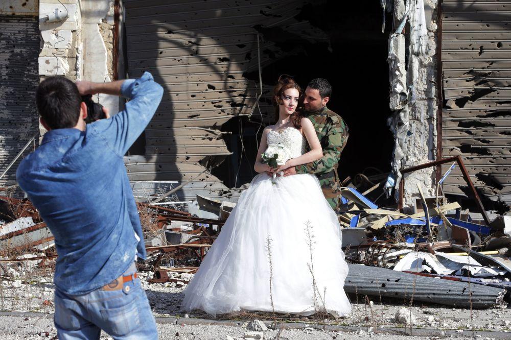 Жас жұбайлар. Батыс Сирия орталығындағы Хомс қаласындағы ғимараттарды лаңкестер қиратқан.