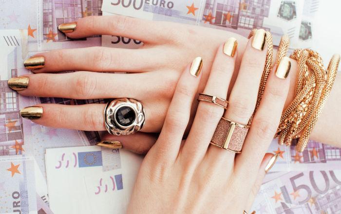 Красивые ухоженные руки с золотым маникюром и в золотых украшениях на фоне евро