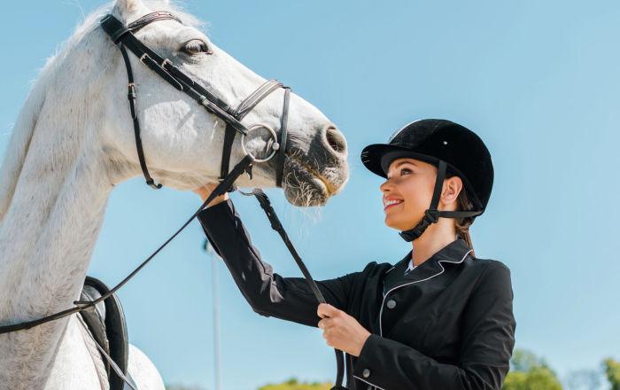 Девушка в костюме для верховой езды стоит рядом с белой лошадью и гладит ее по голове