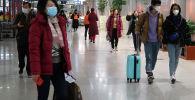 Пассажиры в масках видны в зале терминала международного аэропорта Пекин Столичный в Пекине